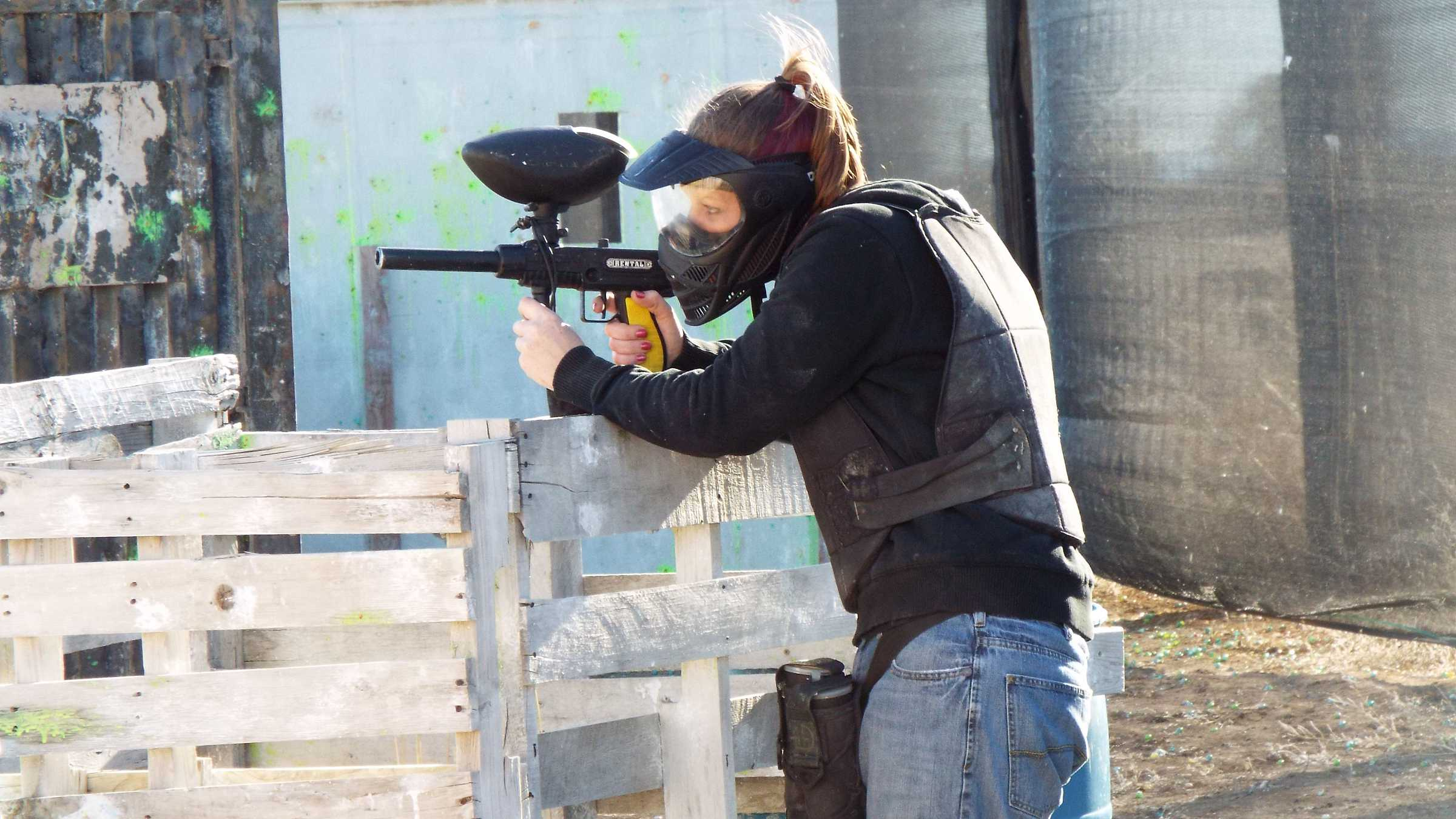 Woman aiming and shooting paintball gun
